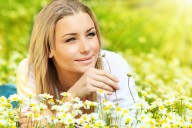 Young beautiful girl laying on the daisy flowers field, outdoor portrait small